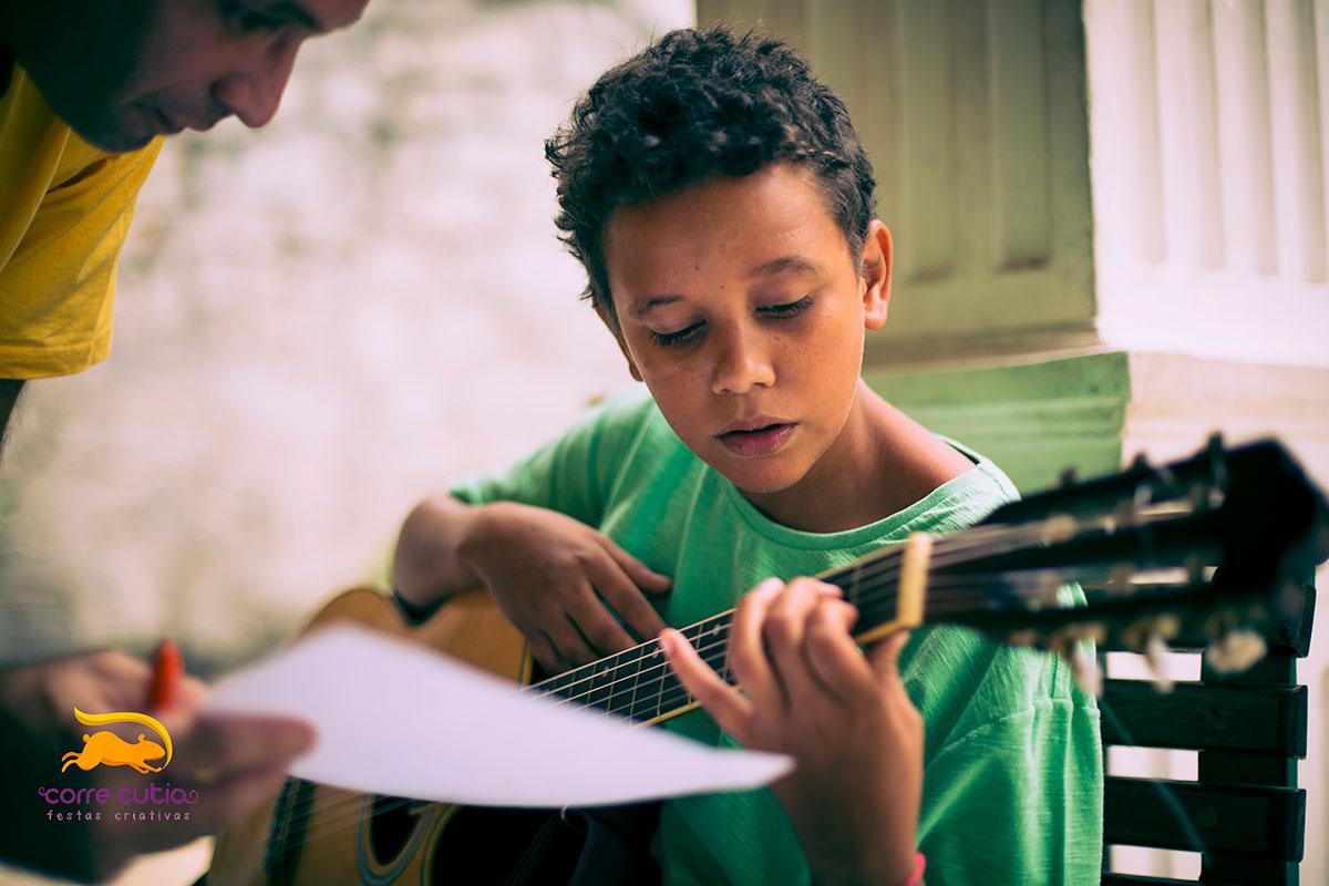 Menino de camisa verde tocando violão